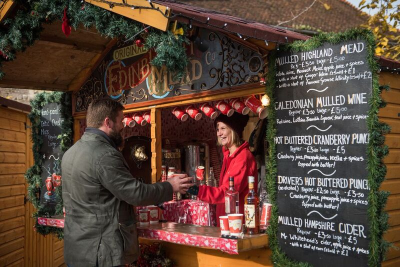 Stall holder serving customer at christmas market