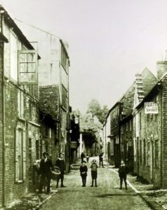 A historic image of people wallking and standing in Houchin Street