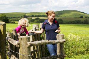 A woman and a little girl passing over a fence with green fields behind them in the South Downs National Park