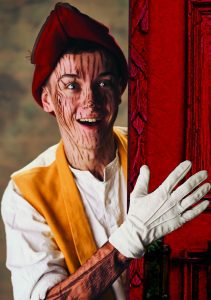 A young man dressed a Pinocchio with face paint to mimic a wood effect peering around a wall