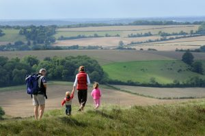 A family of four walking along a grassy hill with a view of the South Downs National Park behind them