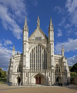 The front of Winchester Cathedral in the sunshine with a blue sky behind it