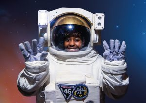 A girl inside a space suit holding up her gloved hands to the camera at the Winchester Science Centre