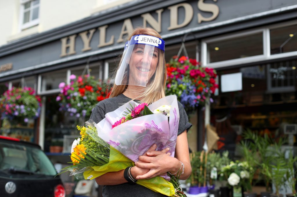 An emplyee standing outside Hylands holding a bunch of flowers