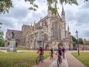 Four people cycle past Winchester Cathedral, one of the largest cathedrals in Europe and one of many impressive historic monuments along King Alfred's Way.