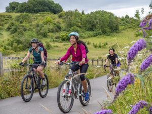 Three women ride into Winchester along the Itchen Way cycle path, past St Catherine's Hill nature reserve. The historic city is the start and end point of King Alfred's Way.