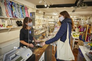 A customer in a mask paying for an item using contactless payment in Cornflowers