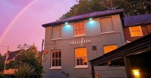 Outside the Railway Inn at sunset with a rainbow in the sky