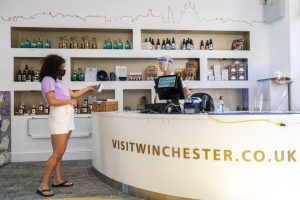 A member of the Winchester visitor information team serving a customer from behind a desk